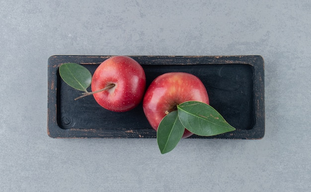 Небольшой поднос с сочными яблоками на мраморе