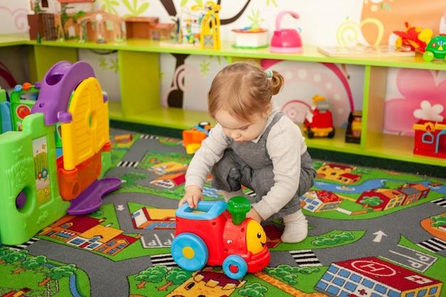 작은 두 살짜리 소녀가 놀이방에서 장난감을 가지고 놀아요.