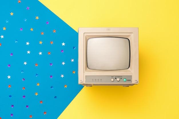 Маленький винтажный монитор на желтом фоне с лучом синего фона и блестками. винтажная электроника. вид сверху.
