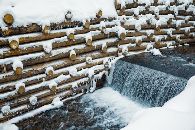 Небольшая стена из бревен ограждает небольшой горный ручей с водопадами в зимнем лесу возле голых деревьев в карпатах.