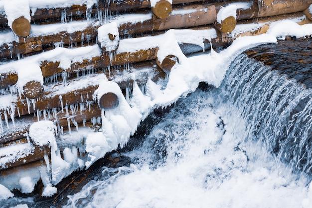 小さな丸太の小さな壁が、カルパティア山脈の裸の木の近くの冬の森の滝のある小さな渓流を囲んでいます。