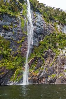 Небольшой водопад с горы фьордленд новой зеландии