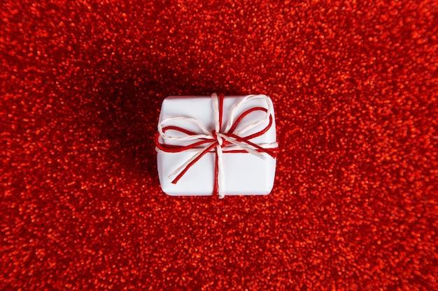 Маленький белый подарок на красном блестящем, сбоку блестки. концепция ко дню святого валентина.