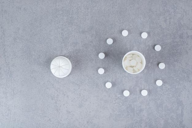 회색 표면에 흰색 알약이 든 작은 흰색 항아리