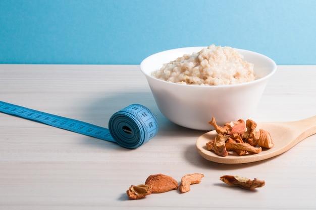 シロップを注いだ、ゆでたオートミールの小さな白いプレート、乾いたリンゴと木製のテーブルの上の青い巻尺の木製の大きなスプーン