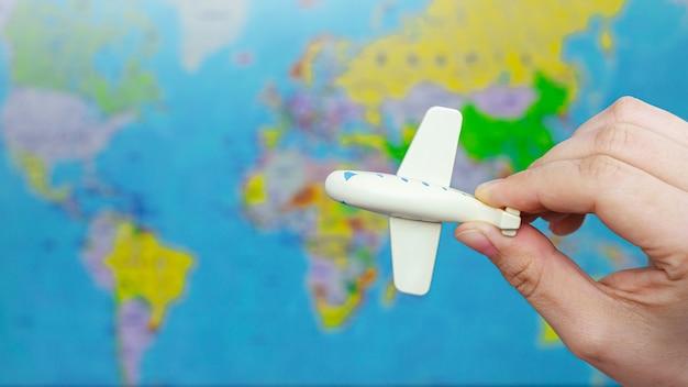 世界地図のぼやけた背景に女性の手で小さな白いおもちゃの飛行機