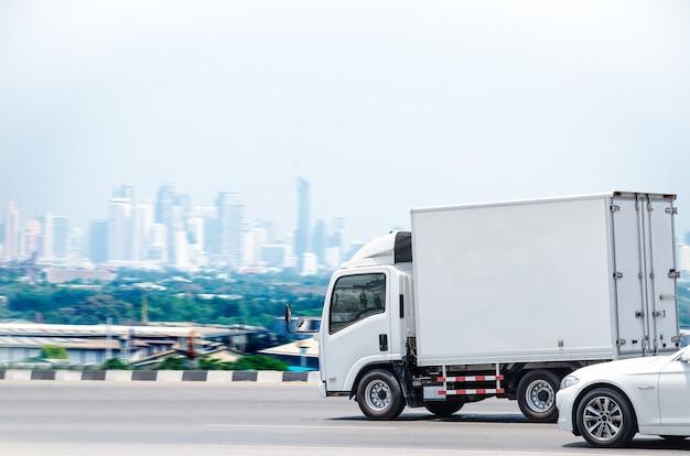 도시 배경의 운송 사업을 위해 도로를 달리는 작은 흰색 트럭.