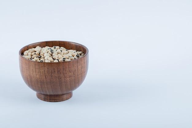 Маленькая деревянная миска, полная сырого белого горошка.