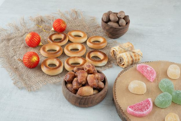 白い背景の上のゼリーキャンディーとドライフルーツの小さな木製のボウル。高品質の写真