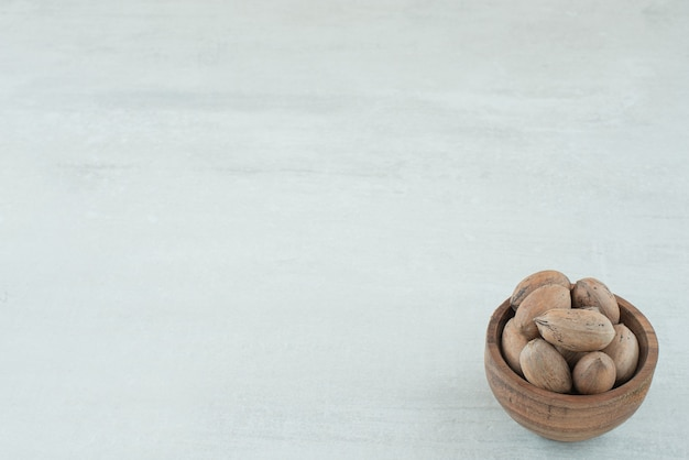 白い背景の上のナッツの小さな木製のボウル。高品質の写真