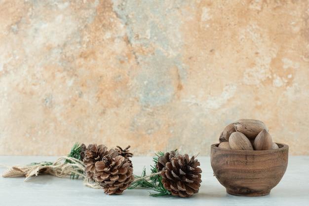白い背景の上の松ぼっくりとナッツの小さな木製のボウル。高品質の写真