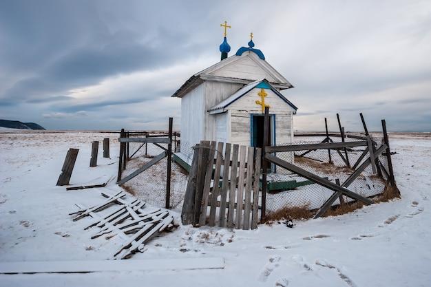 Небольшая деревянная церковь с православными крестами, огороженная старым забором в заснеженном поле