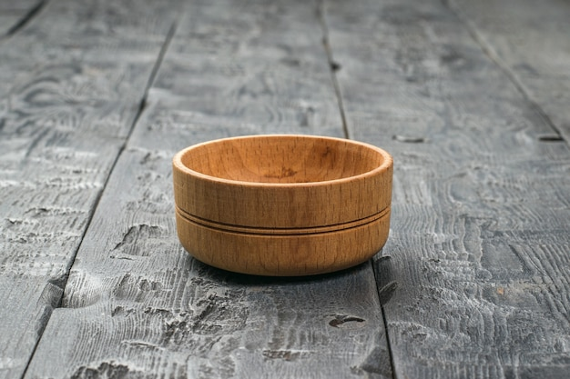 暗い木製のテーブルの上の小さな木製のカップ。素朴な食器。