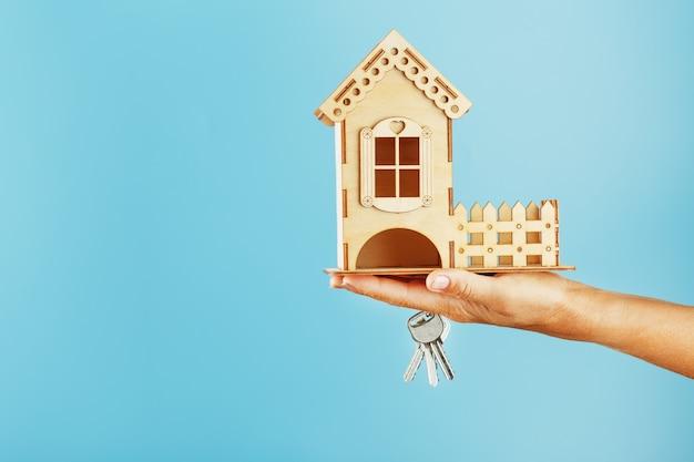青色の背景に手でキーを持つ小さな木の家。