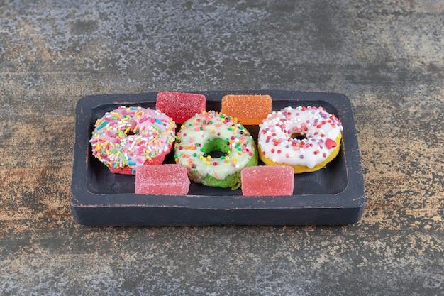 나무 표면에 한입 크기의 도넛과 마멜 레이드를 곁들인 작은 나무 플래터