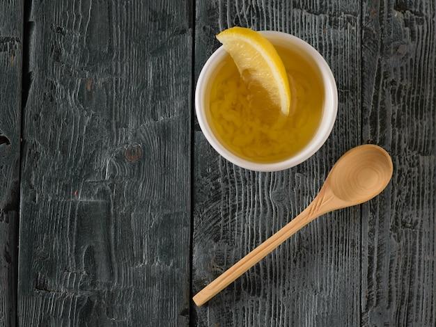 Малая деревянная ложка и чашка оливкового масла и чеснока на черном деревянном столе. заправка для диетического салата. вид сверху.