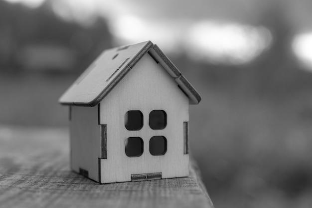 木製のテーブルの端に小さな木のおもちゃの家が立っていて、倒れることがあります。モノクロ。コピースペース