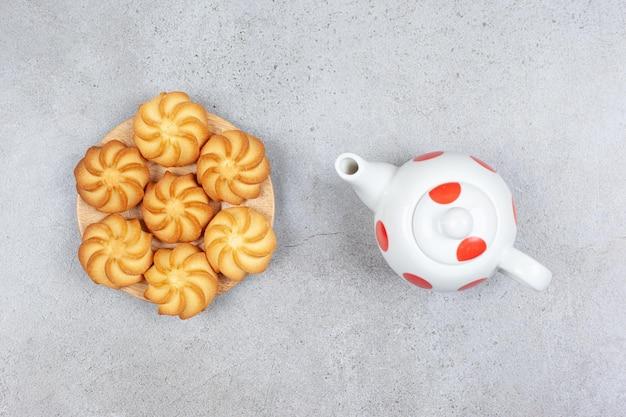 Небольшой деревянный поднос с домашним печеньем и небольшой чайник на мраморной поверхности.
