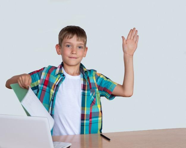 똑똑하고 귀여운 소년이 손을 들고 다른 손에는 숙제가 완료된 공책, 탁자 위에 있는 노트북을 들고 있습니다. 온라인 교육 개념, 다시 학교 개념으로