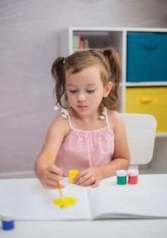 おさげ髪のスマートな女の子がテーブルに座って、子供部屋で絵の具が付いたブラシでアルバムを描いています。
