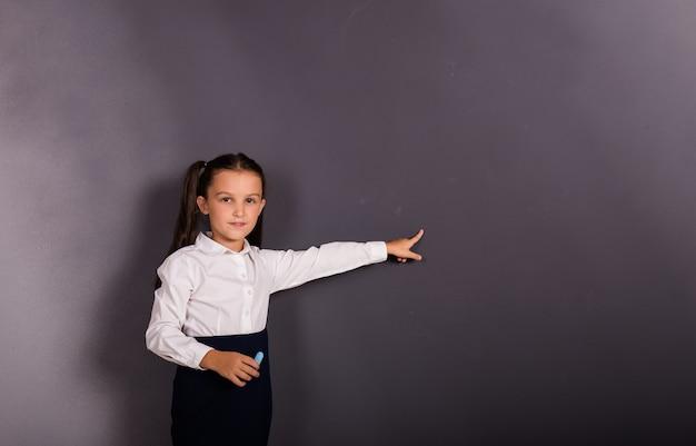 교복을 입은 똑똑한 여학생이 텍스트를 위한 장소가 있는 검정색 배경에 손을 대고 가리키고 있다