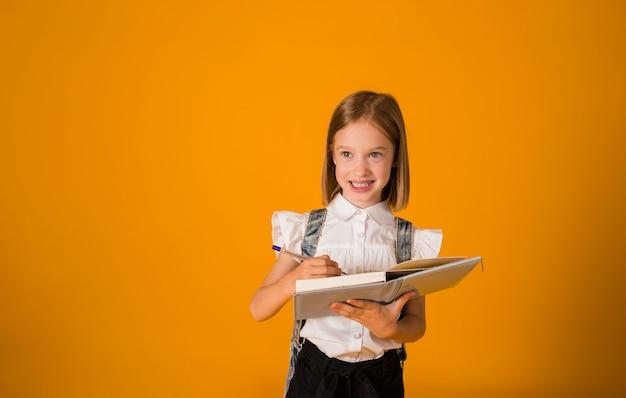 교복을 입은 똑똑한 여학생이 노란색 배경에 펜이 달린 공책을 들고 공간 사본을 들고 있습니다. 학교로 돌아가다
