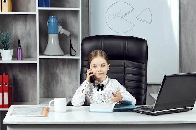 똑똑하고 웃는 어린 소녀가 사무실에서 노트북으로 메모를 하고 전화 통화를 하고 있다
