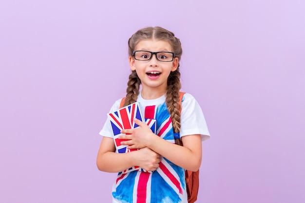 안경을 쓴 똑똑한 학생은 분홍색 외진 배경에 영국 영어 교과서를 손에 들고 있습니다.