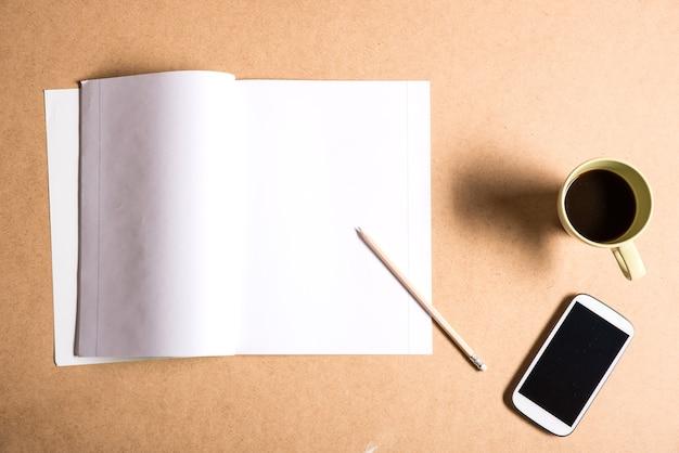 Смартфон и тетрадь на деревянном столе.