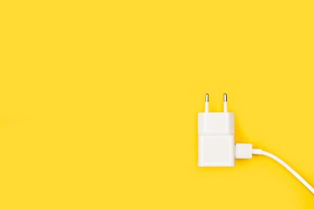 Зарядное устройство для смартфона с кабелем на желтом фоне