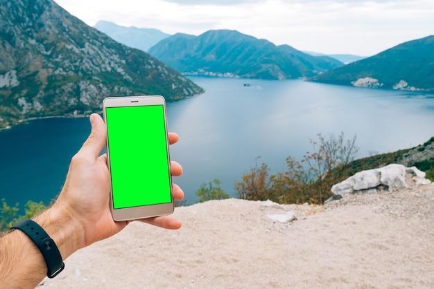 스마트 폰은 손에 녹색 화면이있는 황금색입니다.