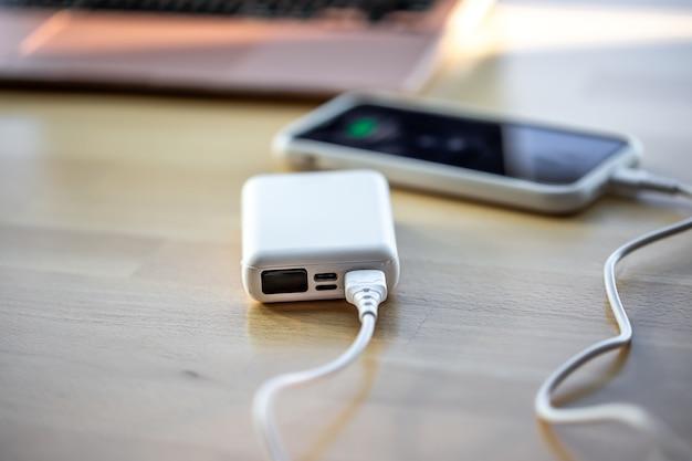 スマートフォンは小さな白いパワーバンクから充電されます