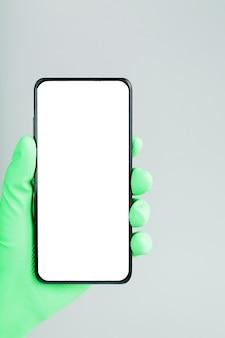 녹색 의료 장갑 클로즈업에서 손에 깨끗한 흰색 화면이있는 스마트 폰