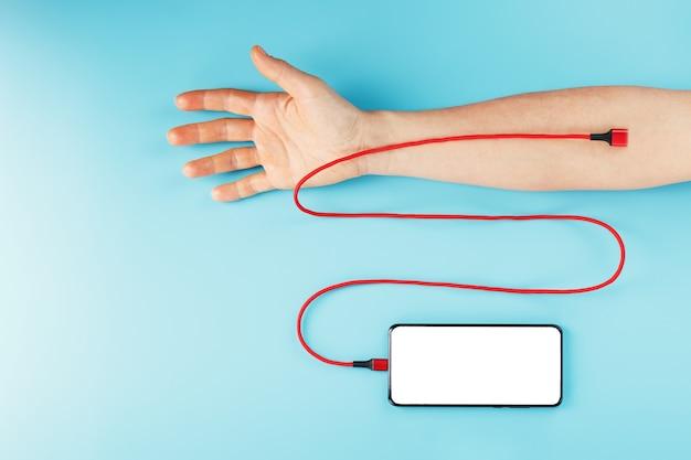 큰 흰색 화면이있는 스마트 폰은 빨간색 usb 코드를 통해 파란색 표면에있는 손의 정맥에 연결됩니다.