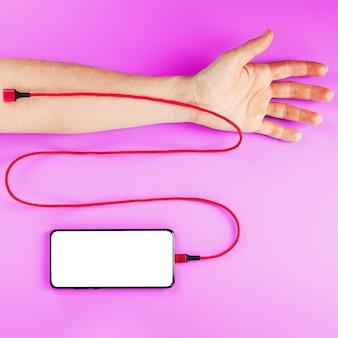 큰 흰색 화면이있는 스마트 폰은 빨간색 usb 코드를 통해 분홍색 표면에있는 손의 정맥에 연결됩니다.