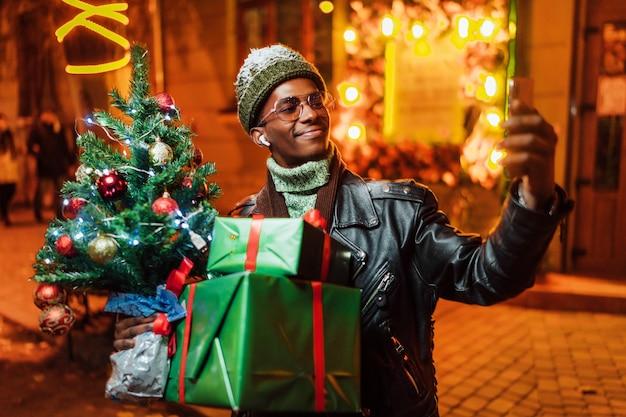 그의 손에 크리스마스 트리와 선물을 가진 웃는 아프리카 계 미국인이 거리에서 셀카를 찍습니다.