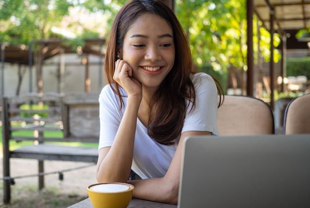 笑顔のアジア人ブロガーがカフェに座って、パソコンでカメラ録画のライブビデオを見ています。オンライン視聴者とのwebカメラビデオ会議の表示。ウェブサイトの作成者と製品のレビュー