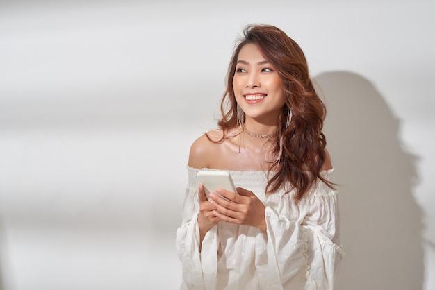 白い背景の上に孤立して立っている間携帯電話で笑顔の魅力的なアジアの女性のテキストメッセージ
