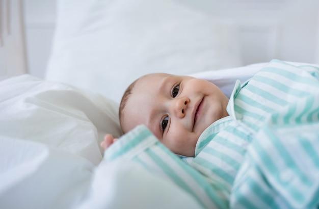 웃는 아기는 침대에 흰색면 담요에 놓여 있습니다.