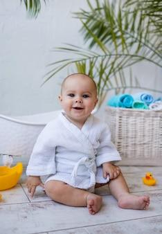 하얀 목욕 가운을 입은 웃고 있는 아기 소녀가 아기 목욕 옆에 고무 장난감 오리와 함께 앉아 있다