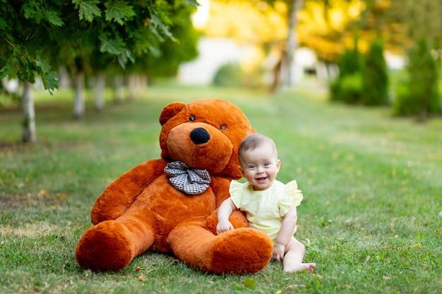 웃는 아기 소녀는 여름에 노란색 여름 드레스에 큰 테디 베어와 함께 푸른 잔디에 앉아있다