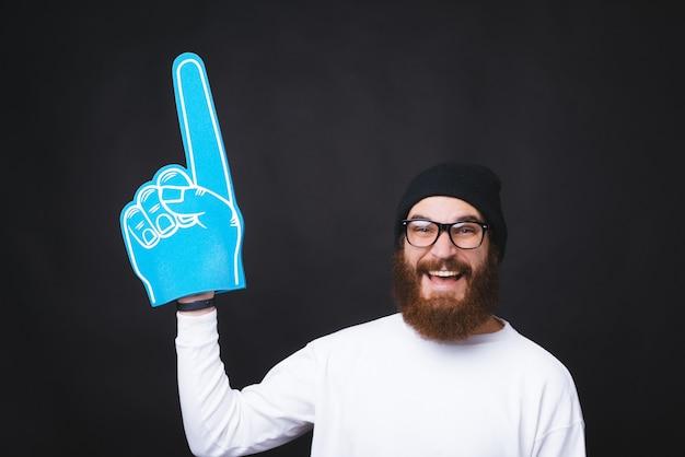 笑顔のバードマンがスペースをコピーするために大きなファンの手袋で指しています。