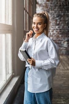 Улыбающаяся блондинка в белой рубашке стоит в офисе у окна и держит в руке черный блокнот.
