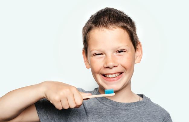 竹の環境にやさしい歯ブラシを持って、彼の歯を見せている笑顔の少年