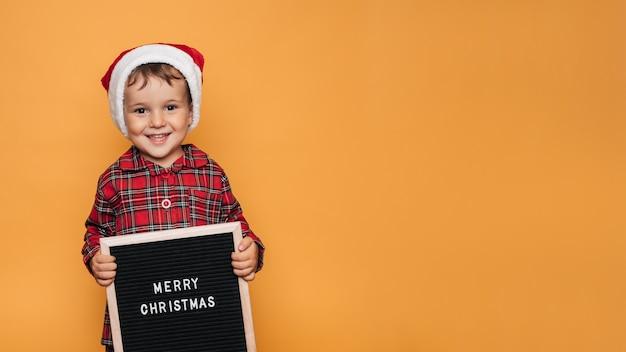 Улыбающийся мальчик в красной шляпе санты и пижаме, с доской с белыми буквами и надписью merry christmas в руках. место для вашего текста и рекламы.