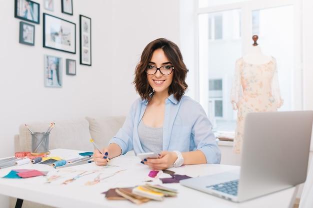 青いシャツを着た笑顔のブルネットの少女は、スタジオのテーブルに座っています。彼女は鉛筆で描いています。彼女はカメラに微笑んでいます。
