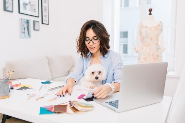 青いシャツを着た笑顔のブルネットの少女は、スタジオのテーブルに座っています。彼女はクリエイティブなものを扱っています。彼女は膝の上に素敵な犬を飼っています。