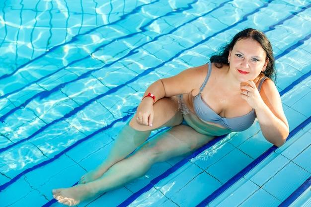 Улыбающаяся брюнетка в купальнике лежит в бассейне, опираясь на руку.