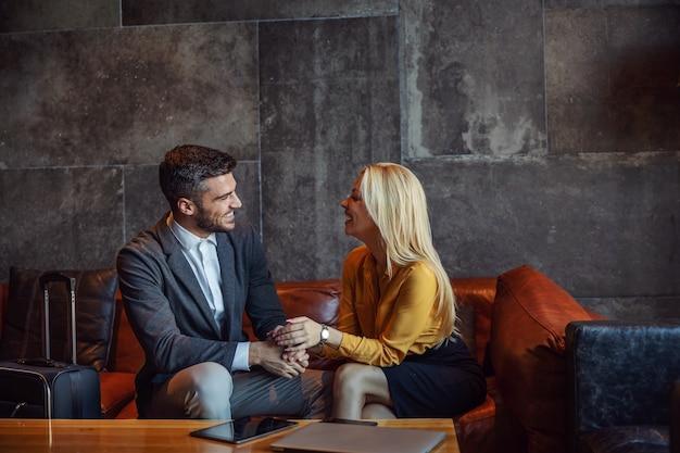 Улыбающаяся деловая пара сидит в холле отеля и разговаривает в ожидании регистрации. на столе телефон, ноутбук и планшет. командировка