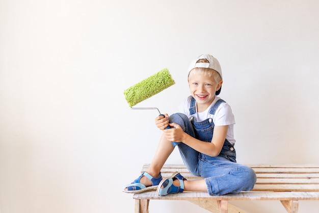 Улыбающийся ребенок-строитель сидит на строительной лестнице в квартире с белыми стенами и держит сруб для покраски стен, место для текста, концепцию ремонта